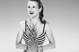 happy woman on seashore with pineapple looking into distance
