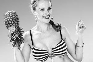 smiling woman in beachwear on beach dancing with pineapple