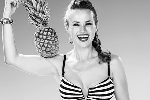 happy fit woman on seacoast showing pineapple biceps