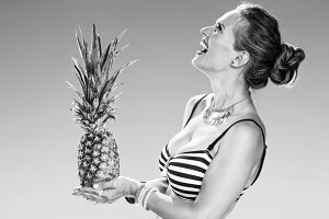 smiling woman on seacoast with pineapple looking at copy space
