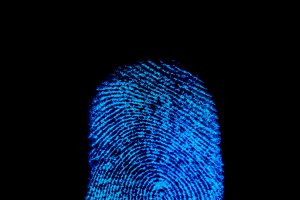 Blue fingerprint identification symbol isolated on black background in technology concept