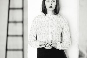Photo of young brunette in blouse near wall