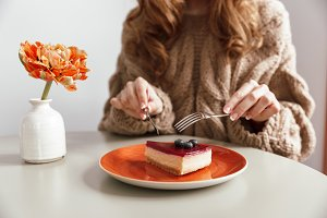 Close up of a woman in sweater eating cheesecake