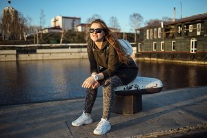 Urban style and fashion concept. Outdoor portrait of beautiful stylish young European female model with long brown hair wearing trendy hoodie, sunglasses, white sneackers and white watches, posing near river enbankment