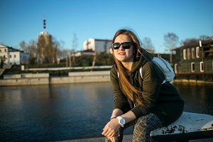 Urban style and fashion concept. Outdoor portrait of beautiful stylish young European female model with long brown hair wearing trendy hoodie, sunglasses, white watches, posing near river embankment