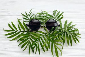 black sunglasses on green palmleaves