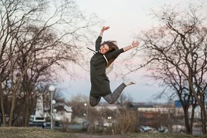 Happiness and freedom concept. Outdoor portrait of beautiful stylish young European female model with long brown hair wearing trendy hoodie and white sneackers watches, jumping in evening autumn or spring park