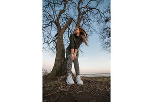 Urban style and fashion concept. Outdoor portrait of beautiful stylish young European female model with long brown hair wearing trendy hoodie and white sneackers watches, posing in evening autumn or spring park.