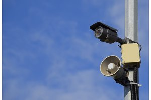 CCTV camera and loudspeaker alarm on a pole against a blue sky.