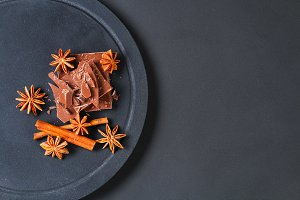 Pieces of chocolate, cinnamon and star anise on a dark grey table.