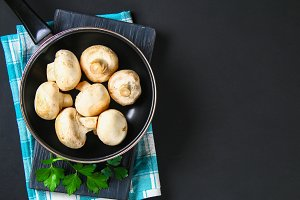 White fresh champignons with parsley on a wooden board on a gray dark table. Mushrooms. Copy the space. Top view.