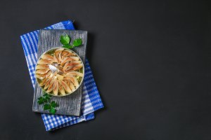Marinated herring in oil on a wooden board on a gray dark table. Snack. Top view. Copy space.