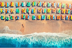 Aerial view of lying woman on the beach with colorful chaise-lounges