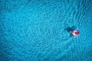 Aerial view of young woman swimming in the sea with transparent water