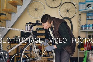 Handsome male mechanic is repairing wheel of bicycle with professional tool while working alone in small workshop with equipment and spare parts visible.