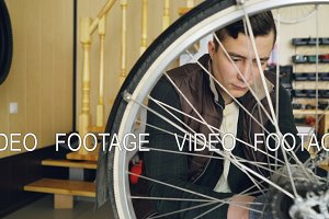 Young man experienced serviceman is fixing bike wheel using wrench and tools. Small cozy workshop interior with wooden walls and ladder, spare parts and equipment are visible.