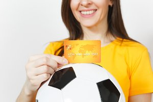 Close up cropped European young woman, football fan or player in yellow uniform holding credit card soccer ball isolated on white background. Sport, play football game, excitement lifestyle concept.
