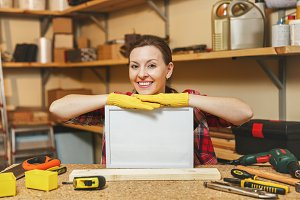 Young woman in plaid shirt, gray T-shirt, yellow gloves working in carpentry workshop at wooden table place with blank frame, different tools. With empty place for text. Copy space for advertisement.