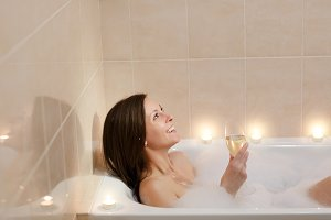Beautiful young sexy woman with long brown hair and straight naked body lying and relaxing in white foam bath tub with candles around in light bathroom, drink alcohol from wine glass indoors.