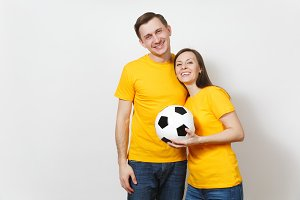 Fun smiling cheerful emotional young couple, woman, man, football fans in yellow uniform cheer up support team with soccer ball isolated on white background. Sport, family leisure, lifestyle concept.