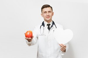 Handsome young doctor man isolated on white background. Male doctor in medical uniform, stethoscope holding red apple, white heart. Healthcare personnel, medicine concept. Proper nutrition. Copy space