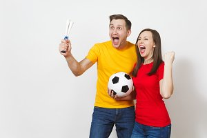 Fun crazy cheerful young couple, woman, man, football fans in yellow and red uniform cheer up support team with pipe soccer ball isolated on white background. Sport, family leisure, lifestyle concept.