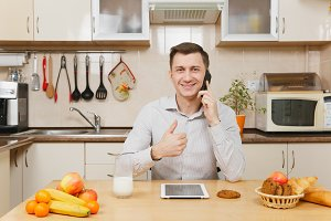 Handsome young business man in plaid shirt having breakfast, sitting at table with tablet, talking on mobile phone, eating cereals with milk on light kitchen. Healthy lifestyle. Cooking food at home.