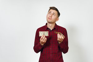 Handsome sad confused annoyed crying caucasian young business man in red shirt holding few banknotes money on white background isolated for advertisement. Concept of poverty and economy.
