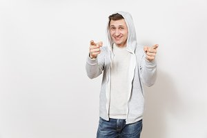 Young handsome smiling man student in t-shirt, blue jeans and light sweatshirt shows a gesture fingers in the camera and rejoices in the studio on white background. Concept of emotions, good mood