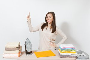 Young housewife in light clothes ironing family clothing, towels on ironing board with iron. Woman pointing index finger up isolated on white background. Housekeeping concept Copy space advertisement.