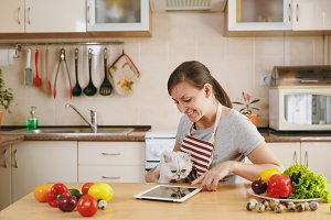 A young pretty woman with white persian cat in the kitchen with tablet on the table. Vegetable salad. Dieting concept. Healthy lifestyle. Cooking at home. Prepare food.