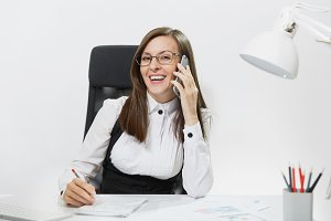 Pretty smiling business woman in suit sitting at the desk, working at contemporary computer with document in light office, talking on mobile phone, conducting pleasant conversation on white background