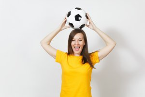 Beautiful European young cheerful woman, football fan or player in yellow uniform holding above head soccer ball isolated on white background. Sport, play football, health, healthy lifestyle concept.