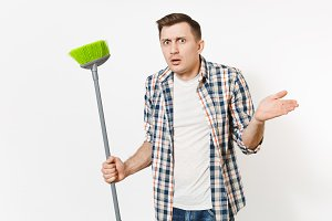 Young strange fun housekeeper man in checkered shirt holding and sweeping with green broom isolated on white background. Male doing house chores. Copy space for advertisement. Cleanliness concept.
