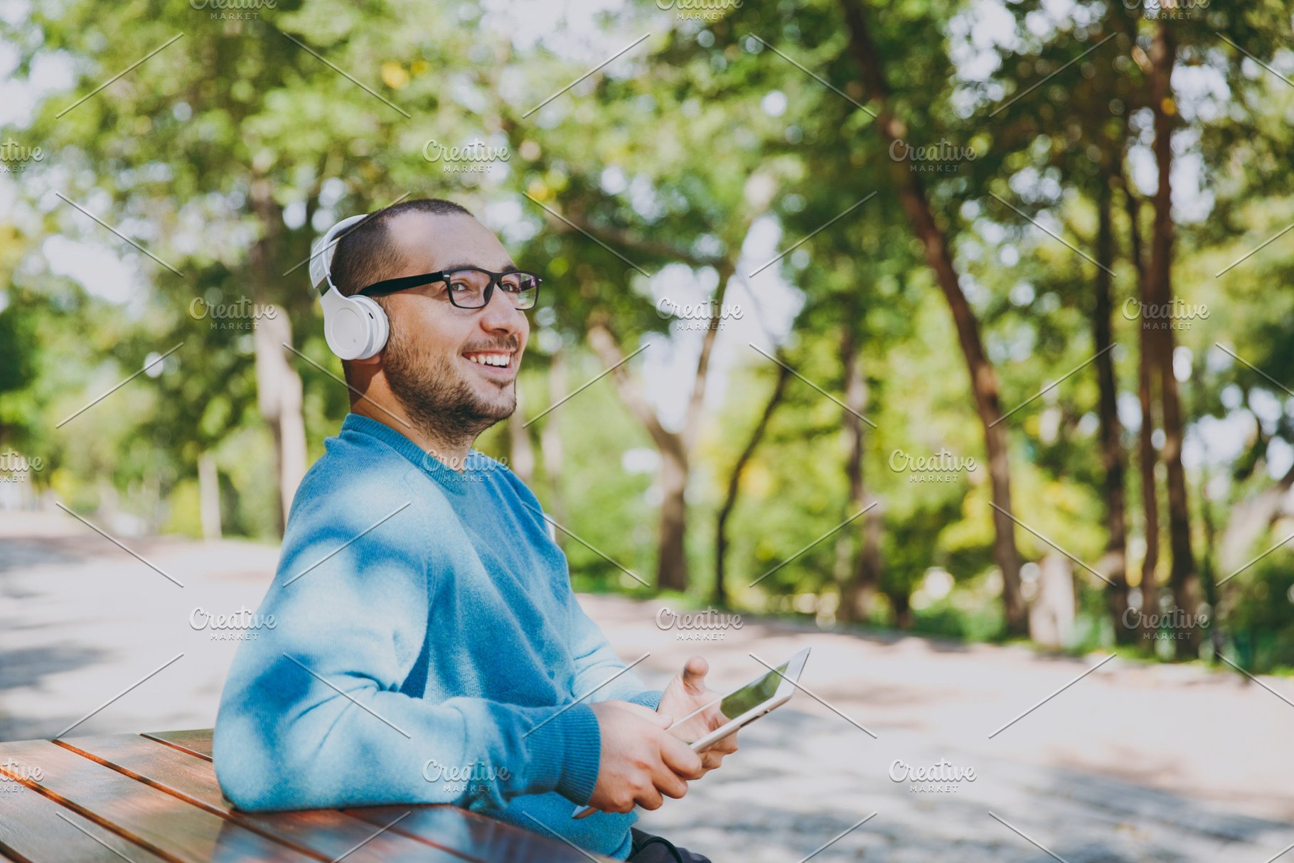 Young Happy Man Businessman Or Student In Casual Blue Shirt Glasses Sitting At Table With Headphones Tablet Pc In City Park Listen Music Rest