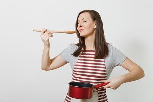 Young smiling caucasian housewife in striped apron, gray t-shirt isolated on white background. Beautiful housekeeper woman holding tasting red empty stewpan wooden spoon. Copy space for advertisement.