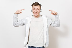Young handsome smiling man student in t-shirt light sweatshirt listening to music with white wireless headphones and shows his index fingers on them in studio on white background. Concept of emotions