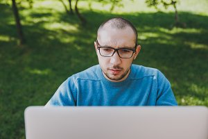 Close up photo young successful smart man businessman or student in casual blue shirt, glasses sitting at table in city park, using laptop, working outdoors. Mobile Office concept. Copy space.