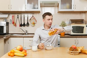 Late caucasian young business man in plaid shirt having breakfast, sitting and looking clock, eating cereals and croissant with milk on light kitchen. Healthy lifestyle. Cooking at home. Prepare food.