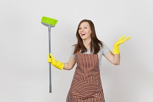 Young smiling housewife in striped apron, yellow gloves isolated on white background. Housekeeper woman cleaning maid holding and sweeping with the broom. Copy space for advertisement Advertising area