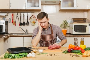 Sad upset caucasian young man in apron sitting at table with vegetables, cooking at home preparing meat stake from pork, beef or lamb, in light kitchen with wooden surface, full of fancy kitchenware.