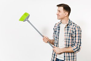 Young housekeeper man in checkered shirt holding and sweeping with green broom isolated on white background. Male doing house chores, looking aside. Copy space for advertisement. Cleanliness concept.