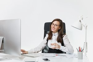 Beautiful smiling brown-hair business woman in suit and glasses sitting at the desk with glass of pure water, working at computer with modern monitor with documents in light office on white background