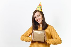 Cheerful caucasian young happy woman in yellow clothes, birthday party hat holding golden gift box with present, celebrating holiday on white background isolated for advertisement. With place for text