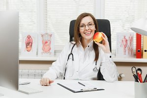 Young smiling female doctor sitting at desk, working on computer with medical documents in light office in hospital. Woman in medical gown with apple in consulting room. Healthcare, medicine concept.