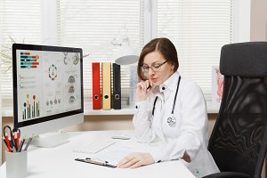 Young woman sitting at desk, working on computer, filling out medical documents in light office in hospital. Female doctor in medical gown, stethoscope in consulting room. Healthcare, medicine concept
