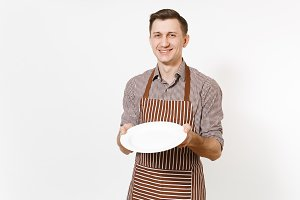 Young man chef or waiter in striped brown apron, shirt holding white round empty clear plate isolated on white background. Male housekeeper or houseworker. Domestic worker copy space for advertisement