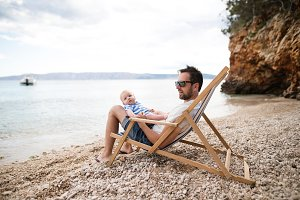 Man with his baby son at the beach, sitting on deckchair