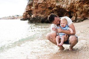 Man with his baby son at the beach having fun.