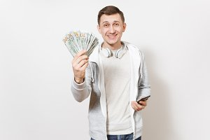 Young handsome smiling man student in t-shirt, light sweatshirt with headphones around neck holds bundle of dollars, cash money, mobile phone in hands isolated on white background. Concept of success.